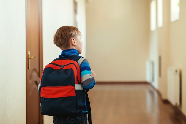 Милый мальчик с рюкзаком собирается в класс. обратно в школу. школьник с рюкзаком в школе, вид сзади.