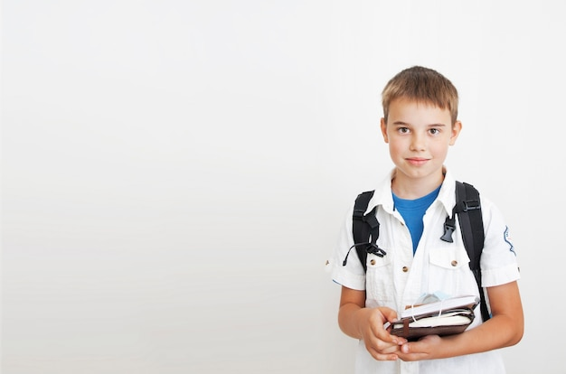 Cute boy with a backpack on a gray background with copy space. in the hands of notebooks and a medical mask. learning, education, school concept