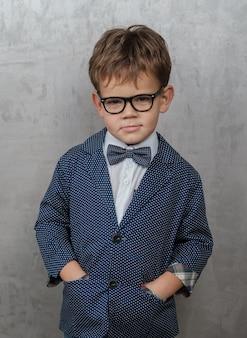 メガネ、水玉模様の青いジャケットと蝶ネクタイとかわいい男の子