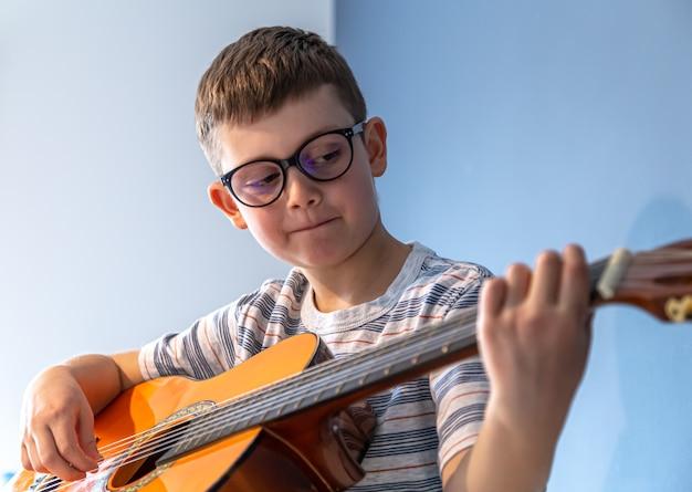 メガネのかわいい男の子が家でクラシック ギターを弾くことを学びます。