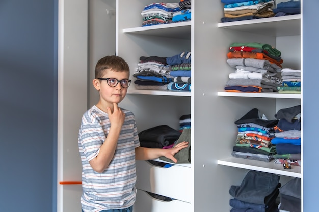 A cute boy with glasses stands near a wardrobe and thinks about what to wear.