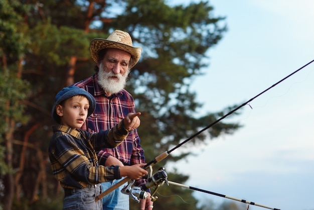 Cute boy with his grey-bearded grandpa catching fish on the lake with landing net at sunset