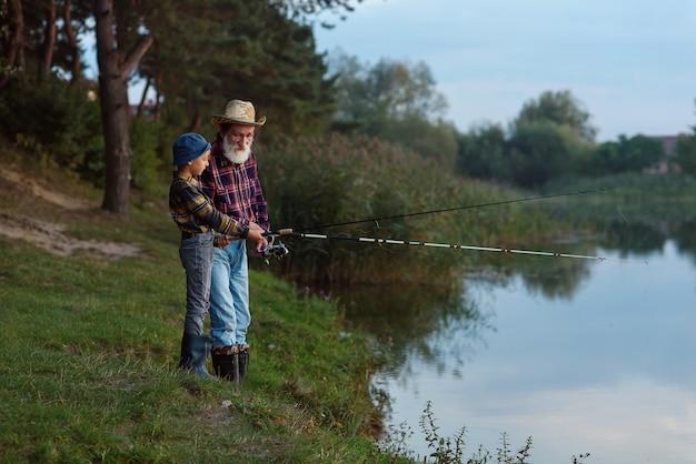 Симпатичный мальчик со своим седобородым дедом ловит рыбу на озере с сеткой на закате
