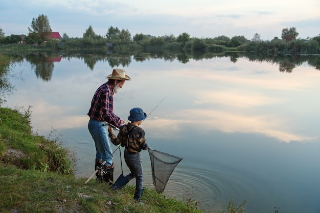 日没時に着陸網で湖で魚を捕まえる彼の灰色のひげを生やしたおじいちゃんとかわいい男の子
