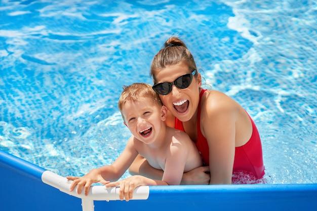 夏の間に水たまりで遊んでいる彼の母親とかわいい男の子