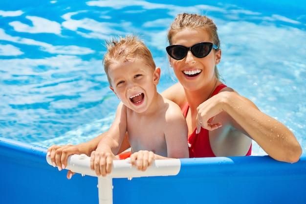 여름 동안 물 수영장에서 노는 그의 어머니와 함께 귀여운 소년