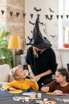Cute boy with paintbrush looking at teacher in witch hat