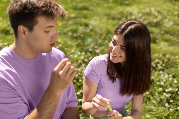 Милый парень и девушка играют с мыльными пузырями