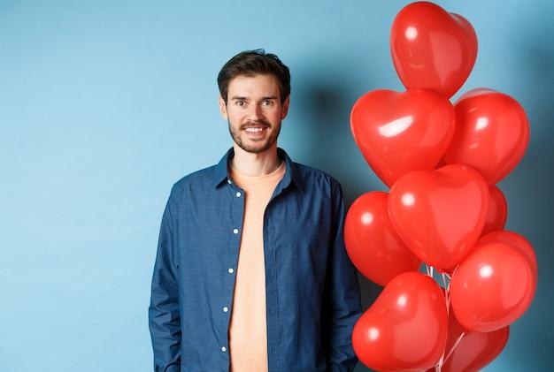 귀여운 남자 친구 찾고 행복 하 고 웃 고, 파란색 배경에 발렌타인 하트 풍선 근처에 서.