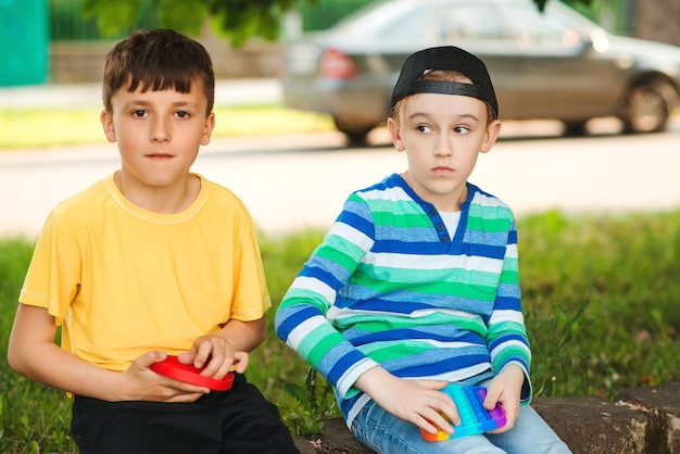 トレンディなポップイットおもちゃで遊ぶかわいい男の子。シリコンの泡のおもちゃで散歩中の友達。屋外で楽しんでいる男の子。子供のための現代の抗ストレス玩具。子供のためのファッション、ライフスタイル、レジャー。