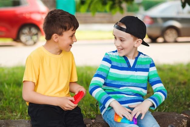 トレンディなポップイットおもちゃで遊ぶかわいい男の子。シリコンの泡のおもちゃで散歩中の友達。屋外で楽しんでいる男の子。子供のための現代の抗ストレス玩具