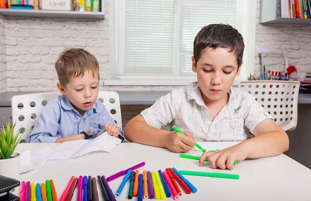 Симпатичные мальчики учатся рисованию в школе счастливая семья рисуют картинки