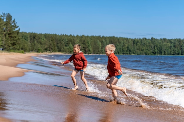 ラドガ湖の波から走る赤いパーカーと青いパンツを着たかわいい男の子