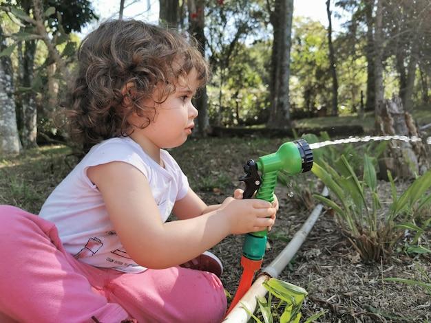 정원에서 물 호스를 가지고 노는 재미 귀여운 브라질 소녀.