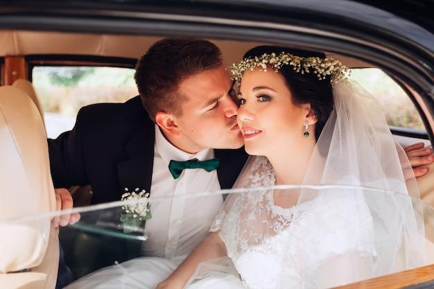 Милая невеста закрыла глаза, а жених целует ее в щеку