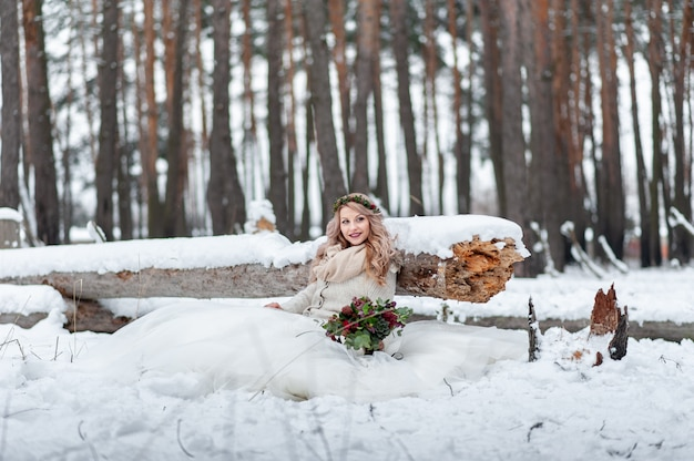 Cute bride of slavic appearance with a wreath holds a bouquet, sits next to the log in the snowy forest. winter wedding ceremony.