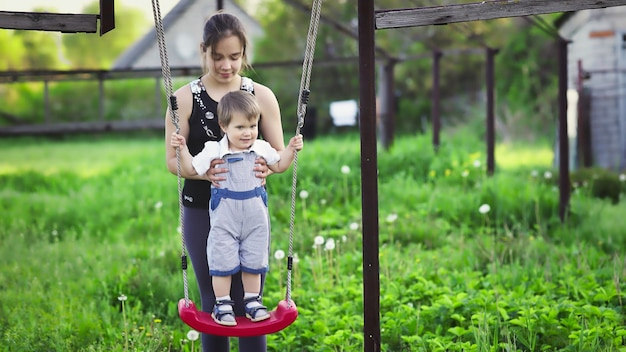 Cute brother and older sister ride on a bright swing on warm spring day against the backdrop of a green blooming garden