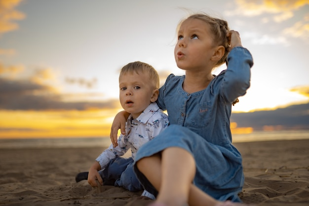 Cute brother and sister sitting on sand at the beach on sunset