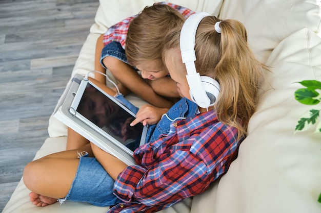 Cute brother and sister with headphones enjoying tablet at home. family, children, technology and home concept