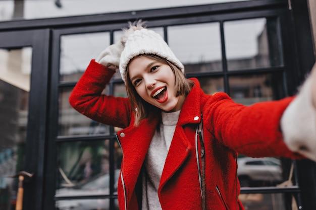 Симпатичная кареглазая девушка в отличном настроении делает селфи. портрет девушки в красной куртке и белой вязаной шапке.