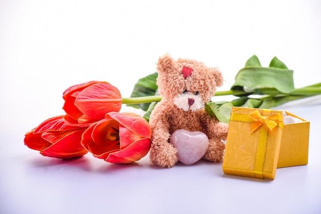 かわいい茶色のテディベア、赤いチューリップの花束、ギフトボックス、バレンタインの日、記念日、クローズアップ