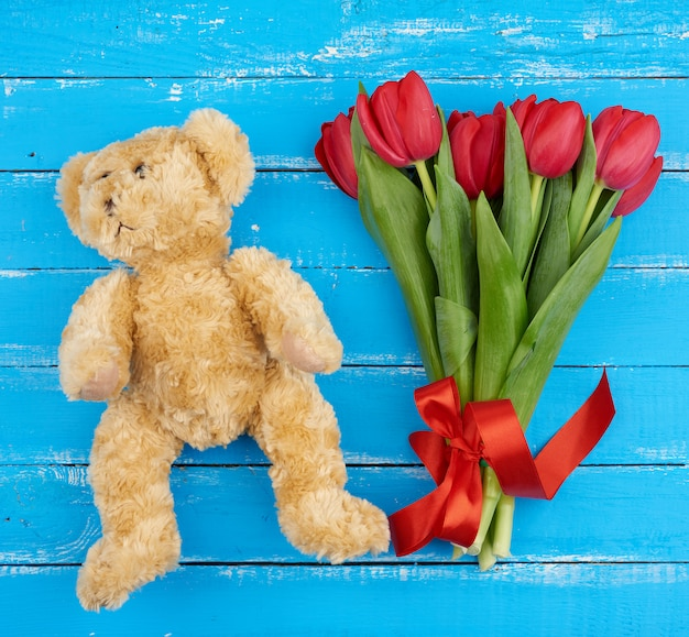 Cute brown teddy bear and bouquet of red blooming tulips with green stems and leaves tied with a red silk ribbon