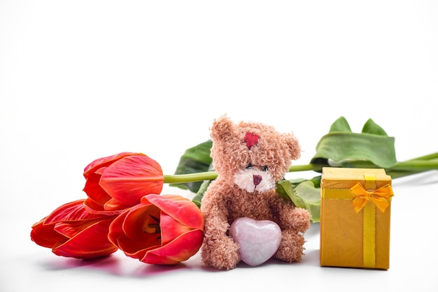 Cute brown teddy bear, bouquet of red tulips, gift box, festive backdrop for birthday