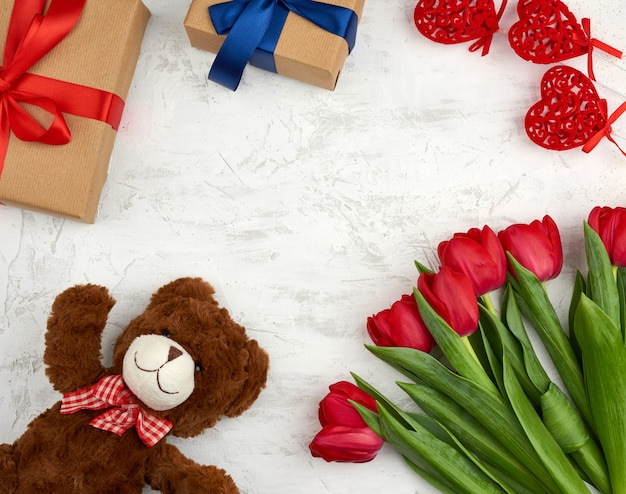 Cute brown teddy bear, bouquet of red tulips, gift box, festive background for birthday