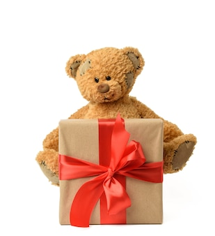 Cute brown teddy bear next to a box with a gift tied with a red silk ribbon on white