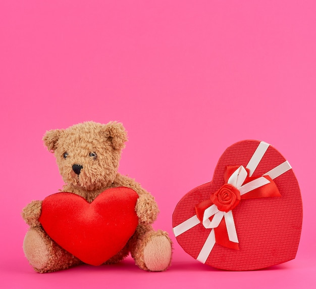 Cute brown teddy bear holding a big red heart and red box