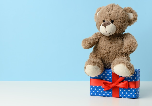 Cute brown teddy bear holding a box wrapped in blue paper and red silk ribbon on white table. prize and congratulations, copy space