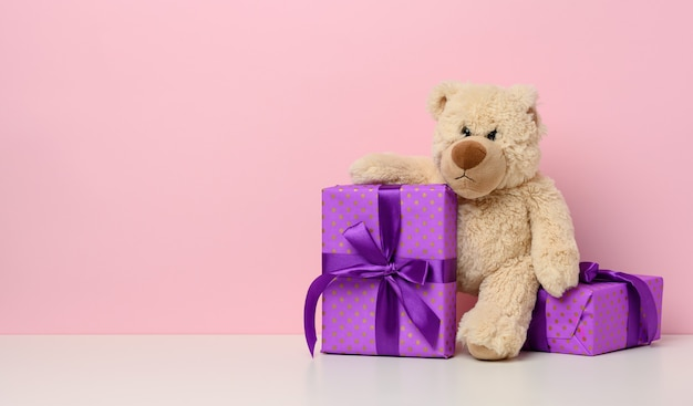 Cute brown teddy bear holding a box wrapped in paper and red silk ribbon on white table. prize and congratulations, pink background, copy space