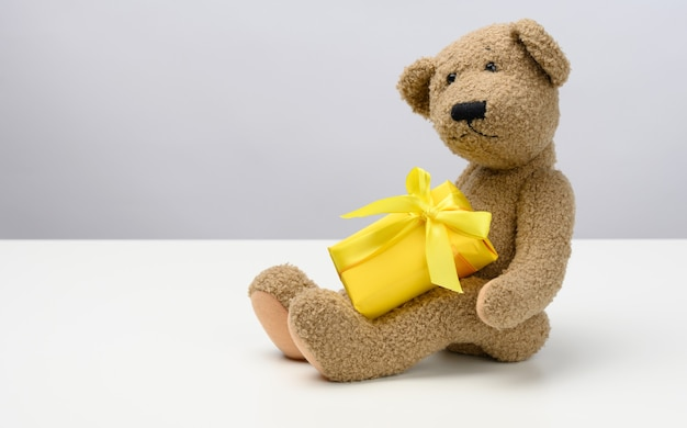 Cute brown teddy bear holding a box wrapped in yellow paper and silk ribbon on white background. prize and congratulations, copy space