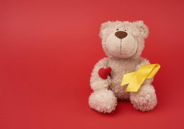 Cute brown teddy bear holds a silk yellow ribbon in the shape of a loop on a red background, concept of the fight against childhood cancer