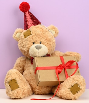 Cute brown teddy bear in a red cap sits and holds a brown box with a gift, festive surface