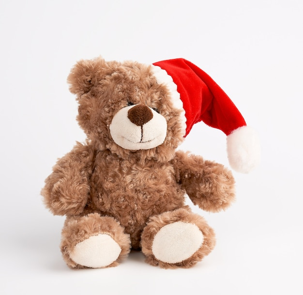 Cute brown teddy bear in a red christmas hat sits