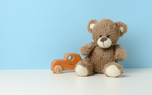 Cute brown teddy bear sits on a white table and a wooden children's toy car, blue background