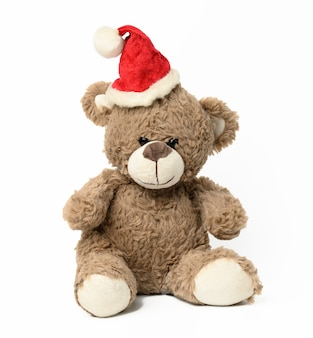 Cute brown teddy bear sitting in red christmas cap on white  background