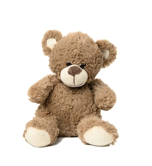 Cute brown teddy bear sitting on white isolated background