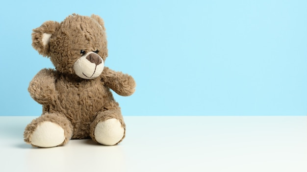 Cute brown teddy bear sitting on a white table, blue background, place for an inscription