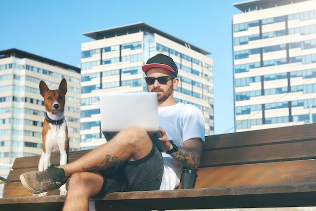 Cane marrone e bianco sveglio che si siede accanto al suo proprietario che lavora su un computer portatile in un parco cittadino