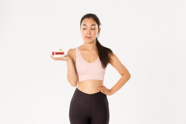 귀여운 갈색 머리 아시아 여자 선수, 맛있는 달콤한 케이크를 먹고 싶지만 다이어트에 유혹, 체중과 칼로리, 흰색 배경을 돌봐주세요.