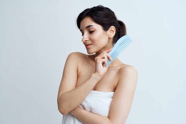 Cute brunette comb hair care naked shoulders light background