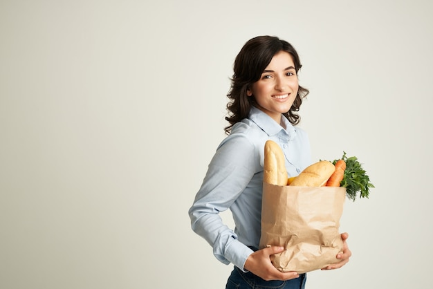 Cute brunette food package supermarket delivery light background