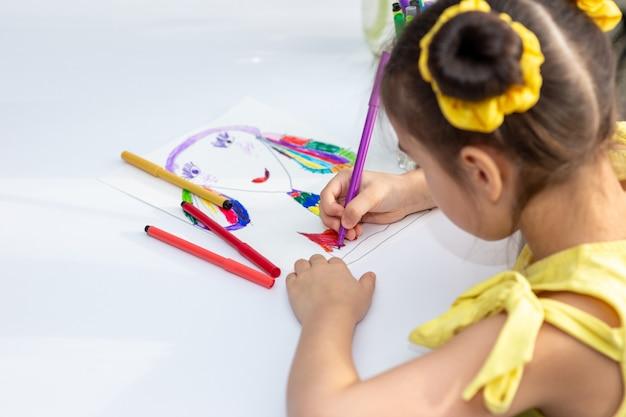 Милая брюнетка девушка в желтом платье рисунок с цветными маркерами.