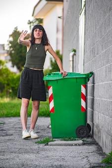 Симпатичная брюнетка девушка возле мусорного контейнера на открытом воздухе