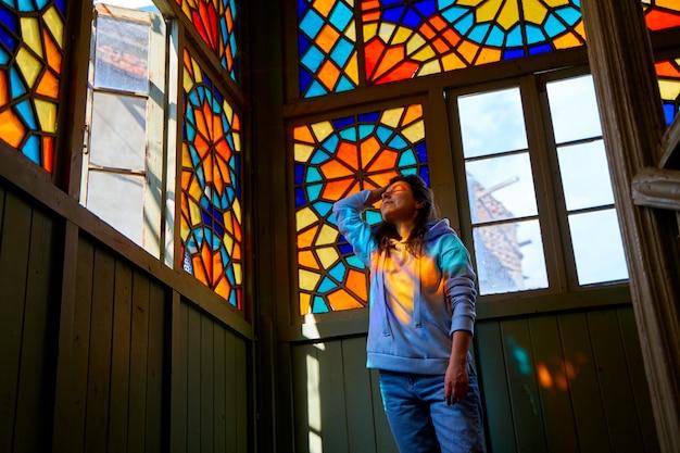여러 가지 빛깔의 모자이크로 만들어진 스테인드 글라스 창문이 있는 오래된 주거용 건물의 정통 발코니에서 포즈를 취한 귀여운 갈색 머리 소녀.