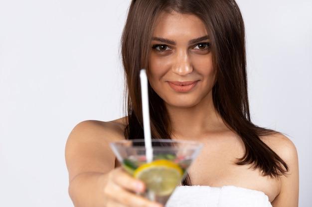 Милая брюнетка девушка позирует с фруктовым коктейлем в руке. изолированный над белой стеной. концепция лета, детоксикации и отпуска. фото высокого качества