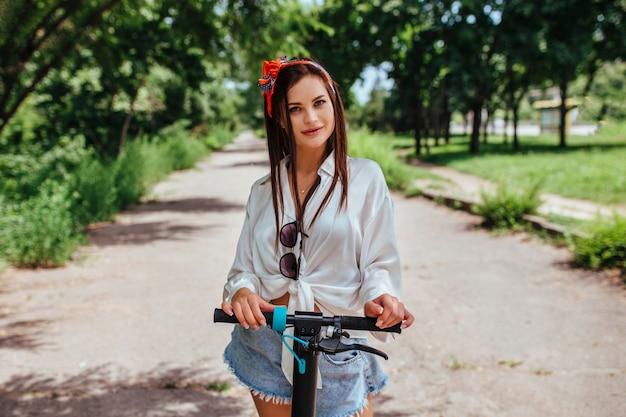 Милая брюнетка девушка катается на самокате электрода в парке, она носит белую рубашку. концепция экологического транспорта и аренды.