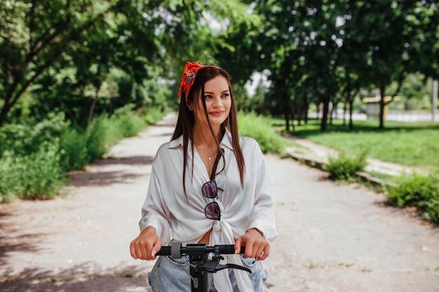 かわいいブルネットの女の子は、白いシャツを着ている公園の電極スクーターに乗っています。エコ輸送と家賃の概念。